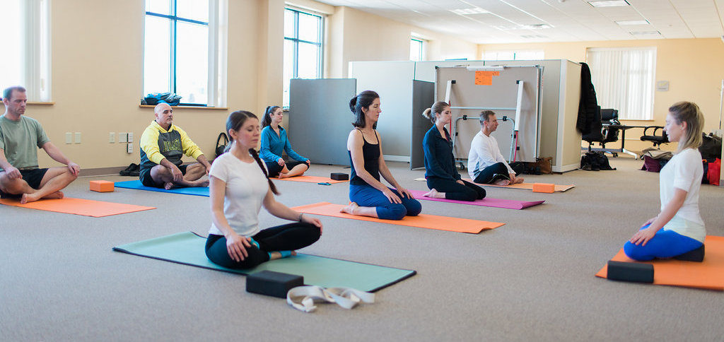 Employees practicing mindfulness before weekly yoga class at Winxnet in Portland, Maine.