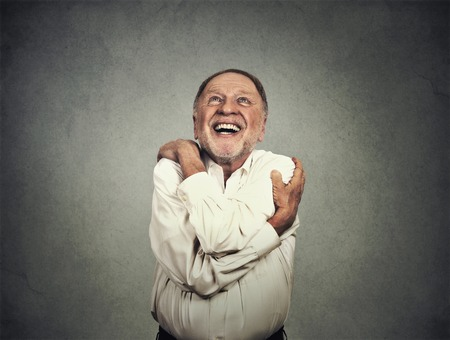 42813357 - closeup portrait confident smiling man holding hugging himself isolated on grey wall background.